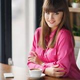 Mädchen mit einer Schale heißem Tee an einem Tisch in einem Café Stockbilder