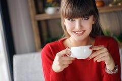 Mädchen mit einer Schale heißem Tee an einem Tisch in einem Café Lizenzfreie Stockbilder
