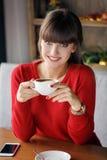Mädchen mit einer Schale heißem Tee an einem Tisch in einem Café Stockfotografie