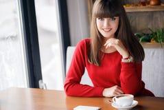 Mädchen mit einer Schale heißem Tee an einem Tisch in einem Café Lizenzfreie Stockfotos