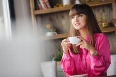 Mädchen mit einer Schale heißem Tee an einem Tisch in einem Café Stockfoto