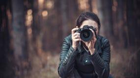 Mädchen mit einer SLR-Kamera in einer schwarzen Jacke stockfotografie