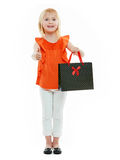 Mädchen mit Einkaufstasche auf dem weißen Hintergrund, der sich Daumen zeigt Lizenzfreies Stockbild