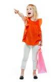 Mädchen mit Einkaufstasche auf weißem Hintergrund zeigend auf etwas Lizenzfreie Stockfotos