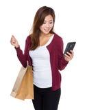 Mädchen mit Einkaufstasche und gelesen der Mitteilung des Mobiltelefons lizenzfreies stockbild