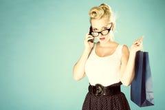 Mädchen mit Einkaufstasche- und Handyretrostil Lizenzfreie Stockfotografie