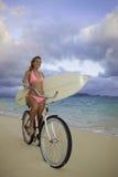 Mädchen mit Fahrrad und Surfbrett Stockfotografie