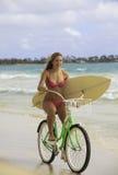 Mädchen mit Fahrrad und Surfbrett Lizenzfreie Stockfotos