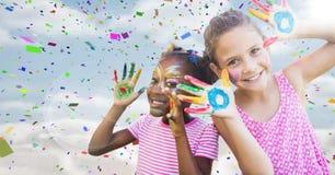 Mädchen mit Farbe auf Händen gegen Himmel mit Aufflackern und Konfettis Stockbilder