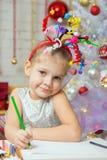 Mädchen mit Feuerwerken eines Spielzeugs auf dem Kopf zeichnet Bleistift auf einem Blatt Stockbild