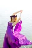 Mädchen mit Flugwesen des lockigen Haares im purpurroten Kleid stockbild