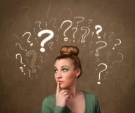 Mädchen mit Fragezeichensymbolen um ihren Kopf Lizenzfreie Stockfotos
