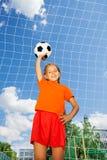 Mädchen mit Fußball steht im vorderen Holzarbeitnetz Stockfotografie