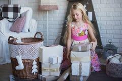 Mädchen mit Geschenkbox in den Händen ist betrachtet Vorbereitung für den Feiertag, Verpackung, Kästen, Weihnachten, neues Jahr,  stockbilder