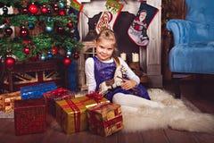 Mädchen mit Geschenken und Spielzeugpferd im Weihnachtsraum Lizenzfreie Stockfotos