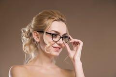 Mädchen mit Gläsern mit der Hand nahe Gesicht Lizenzfreies Stockbild