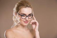 Mädchen mit Gläsern mit der Hand nahe Gesicht Stockfoto