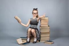 Mädchen mit Gläsern ein Buch lesend Stockfotos