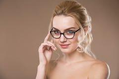 Mädchen mit Gläsern mit der Hand nahe Gesicht Stockfotografie