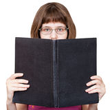 Mädchen mit Gläsern schaut über dem großen lokalisierten Buch Stockfoto