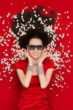 Mädchen mit Gläsern und Popcorn des Kino-3D einen Film aufpassend Stockfoto