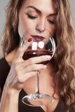 Mädchen mit Glas Rotwein Schöne blonde Frau, die Rotwein trinkt Lizenzfreie Stockfotos