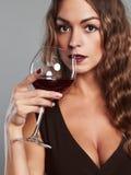 Mädchen mit Glas Rotwein Schöne blonde Frau, die Rotwein trinkt Stockfotografie