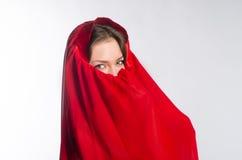 Mädchen mit grünen Augen versteckt ihr Gesicht in einem Schleier Stockbild