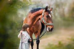 Mädchen mit großem Pferd stockbild