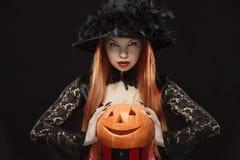 Mädchen mit Halloween-Kürbis auf schwarzem Hintergrund Lizenzfreies Stockfoto