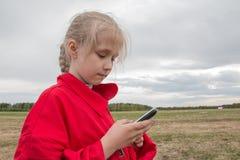 Mädchen mit Handy und bewölktem Himmel Lizenzfreies Stockbild