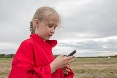 Mädchen mit Handy und bewölktem Himmel Lizenzfreie Stockbilder