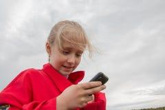 Mädchen mit Handy und bewölktem Himmel Stockfotos