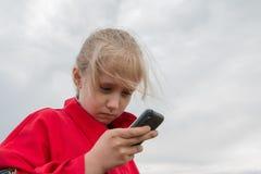Mädchen mit Handy und bewölktem Himmel Lizenzfreie Stockfotografie