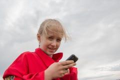 Mädchen mit Handy und bewölktem Himmel Stockbilder