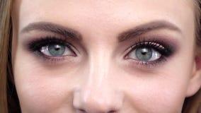 Mädchen mit hellem Make-up blinzelnd in die Kamera Abschluss oben Langsame Bewegung stock video