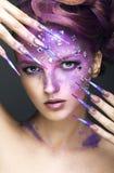 Mädchen mit hellem purpurrotem kreativem Make-up mit Kristallen und langen Nägeln Schönes lächelndes Mädchen Stockbilder