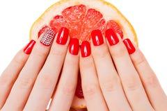 Hände mit roter Nagellüge auf Pampelmuse lizenzfreie stockbilder