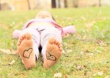 Mädchen mit Herzen auf Sohlen Stockfotografie