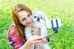 Mädchen mit Hund gemachten Fotos ihrem Selbst, stockfotos