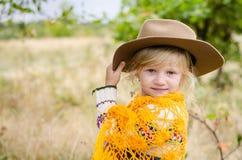 Mädchen mit Hut und orange pelerine in der Herbstsaison Lizenzfreies Stockbild