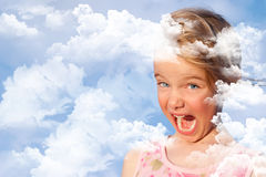 Mädchen mit ihrem Kopf in den Wolken - begrifflich Lizenzfreies Stockfoto