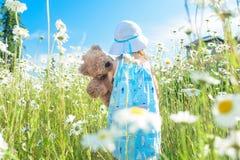 Mädchen mit ihrem Teddybären, der auf dem Gebiet von Gänseblümchen geht Stockbild