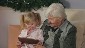 Mädchen mit ihrer Großmutter, welche die Tablettenfotos betrachtet stock footage