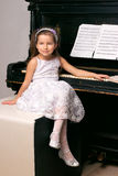 Mädchen in einem schwarzen Kleid, das nahe dem Klavier sitzt Stockbild