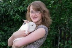 Mädchen mit Kaninchen auf Händen Stockfoto