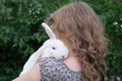 Mädchen mit Kaninchen auf Händen lizenzfreies stockbild