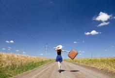 Mädchen mit Koffer an der Landstraße. Stockbilder