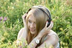 Mädchen mit Kopfhörern auf dem Gras Stockbilder