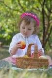 Mädchen mit Korb Pfirsich essend Stockbild